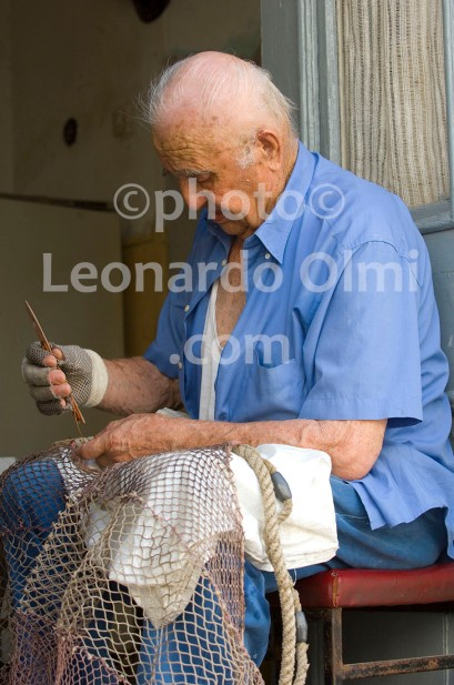 Fisherman repearing his fishing net, Stari Grad; Hvar island; Croatia