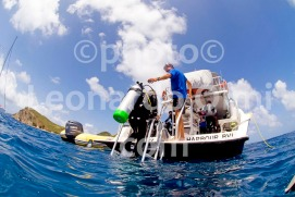 Diver getting back on dive boat at the end of the dive, British Virgin Islands, Caribbean